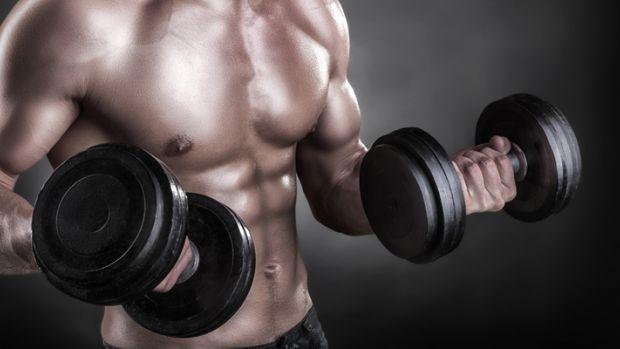 muskuļots vīrietis ar hantelēm